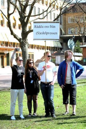 PROTESTER. En liten trupp om fyra motdemonstranter från moderata ungdomsförbundet hukade sig längst bak på Slottstorget.