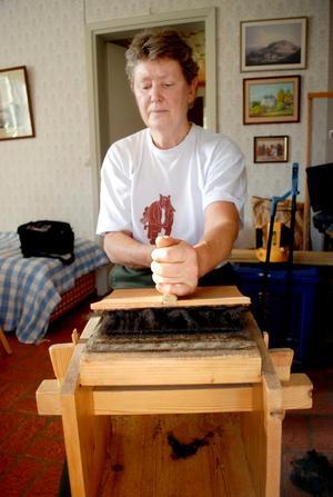 Kardar. Britt Davidsson kardar ullen innan den går att använda för tovning eller för att spinna garn.