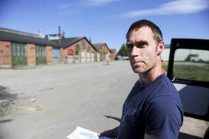 Peter Östman studerar en karta över var misstänkta föroreningar finns. Framför huset i bakgrunden tvättade man tågen förr i tiden, bland annat med det väldigt giftiga ämnet trikloretylen.