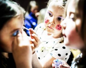 Sofie (i förgrunden till höger) och Nellie hjälper Venla att sminka sig till en av rödluvorna.