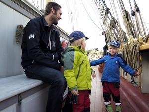 Agust, 3 år, visar för pappa Christoffer Larsson och brorsan Alvar exakt hur lång båt han vill ha efter att ha besökt briggen Tre Kronor.