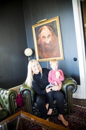 Pernilla och Angcelo framför målningen av Viktors förfader som var konstnär.