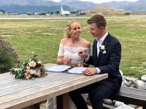 All administration kring bröllopet skedde ute i det fria vid flygplatsen i Queenstown. Här skriver Pernilla och Daniel under vigselpapperna efter vigseln på Coromandel Peak. Foto: Privat