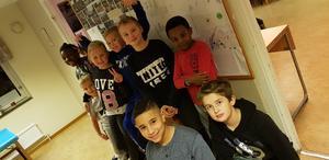 Några av barnen poserar framför sina teckningar.