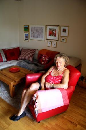 Birgitta i tv-rummet. Den vita mattan har hon vävt själv. Den röda klubbfåtöljen kommer från NK.