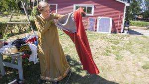 Emelie visar upp en tidstypisk klänning, eller kjortel. – Den här ska Fru Katarina ha på sig, säger hon.