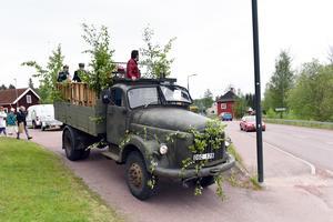 En mörkgrön lastbil av årsmodell 1959 och märket Volvo. På flaket fullt med studenter.