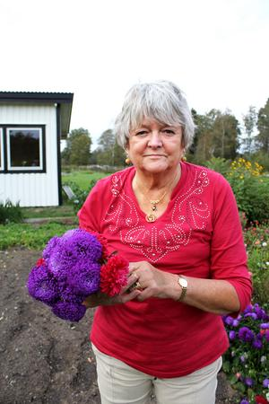 Louise-Marie plockar blommor i trädgården.