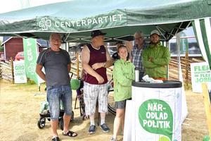 Centerpartiet lockade många, speciellt när regnet brakade lös. På bilden tar Kjell Tenn och Jan Spånberg emot lämpligt grönklädda paret Lotta och Maxime Boujo-Kindlund.