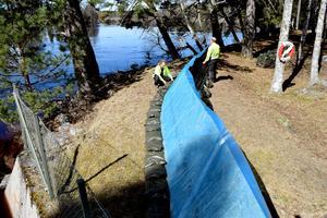 Personal från fastighetsavdelningen har provbyggt en tolv meter lång vall, som beräknas stå emot om vattennivån stger upp till 4 centimeter ovanför jordvallen vid Fänforsen.