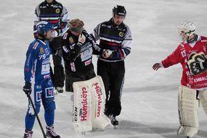 Dennis Nilsson leds av isen efter smällen i huvudet. Vetlandas målvakt Viktor Birgersson är fram och klappar om.