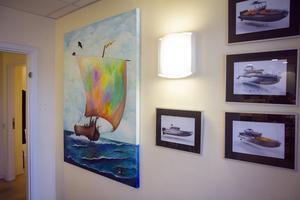 I entrén hänger bilder på de egna båtmodellerna, och Charlotte Winbergs målning av ett vikingaskepp – de tusen år gamla skeppen har inspirerat till SSY:s båtkonstruktion.
