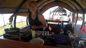 Maria Lindell, Ilsbo, lagar mat i den hästdragna vagnen vid forböndernas sommarresa runt Norrdellen.