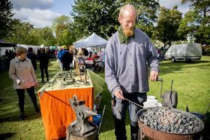 Smeden Jonas Öhlén med sin mobila ässja och konstsmidet på bordet intill.
