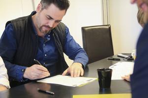 Magnus Olofsson, ägare av Kitchen skriver på avtal där han nu anställer två elever.
