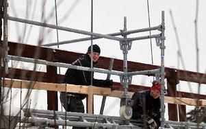 Alf Isacsson och Andreas Olars monterar ihop byggnadsställningen ute på bron.