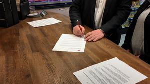 Peter Hultqvist (S) signerar överenskommelsen.