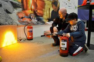 Tioårige Eric Sjölander släckte en digital brand med hjälp av Jens Grelsson från räddningstjänsten.