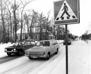 En militärskyltad Volvo och en Ford Taunus har stannat vid övergångsstället vid Ahlbergshallen i november 1975.