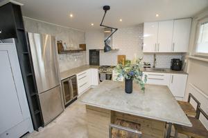 Öppet kök med ytor av betong, järn och trä.