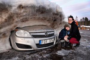 Sonja Sandberg och sonen Liam vid sin bil där fronten nu börjat tina fram i vårsolen. I övrigt är den täckt av ett tjockt snölager.
