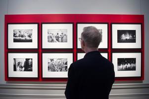 Utställningschefen Per Hedström betraktar Jean-Claude Coutausses fotografier från Berlinmurens fall. Foto:  Henrik Montgomery / TT