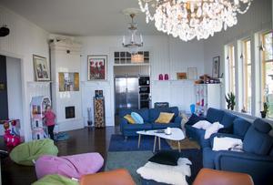 I det rymliga vardagsrummet finns en fungerande kakelugn. Den höga panelen är i original men nymålad.