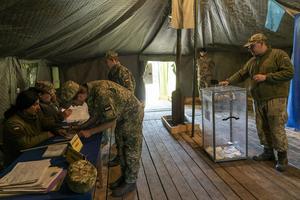 Bild från presidentvalet i maj. Soldater vid fronten i östra delarna av landet röstar. AP Photo/Evgeniy Maloletka