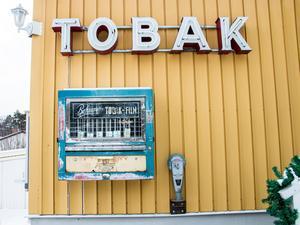 På husväggen hänger en neonskylt, en tobaksautomat och en gammal parkeringsautomat.
