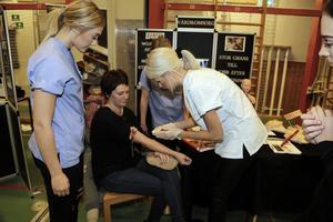 Alice Lundholm (th) tar ett prov på Anneli Strindin (lärare) under överseende av en annan elev, Tova Mårdberg.