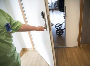 En undersköterska gläntar på en dörr till ett boende på ett äldreboende. Foto: Fredrik Sandberg / TT