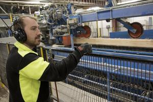 Sågaren Anders Lundquist rör sig ute runt sågen. Han kontrollerar och serverar processen medan kollegan Tobias Karlström övervakar allt på bildskärmar inne i manöverrummet intill såghallen.