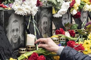 Blommor och ljus vid bilder av de som dog på Majdan 2014. AP Photo/Evgeniy Maloletka.