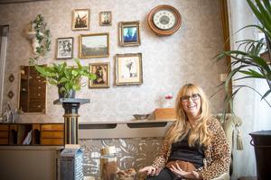 På den ena väggen har Catharina privata foton i snirkliga ramar.