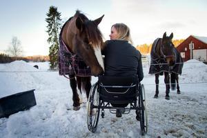 Matilda Persson tillsammans med kallblodshästen Linna i hagen hemma på gården. Alla Matildas hästar har alltid accepterat rullstolen.