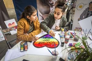 Bästisarna Magdalena och Julia målar pride-skyltar med Juvenitas ungdomsjour på Södertäljefestivalen.