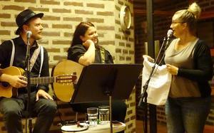Erika Sjödin överlämnar en gåva som visar på hur värdefulla kvällens underhållare är då de sprider glädje på Café Kyrkbacken.