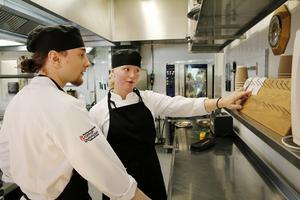 Rebecka Forsberg och klasskompisen Edwin Ramsay kollar beställningarna.