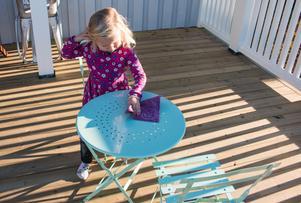 Nelly, 3, torkar rent bordet som står på den nybyggda terrassen.