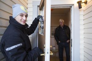 """Glasmästaren Anton Leosson byter glas i dörren där inbrottstjuven tog sig in. Inomhus står Jan-Olov Segevall: """"Det här kanske påminner övriga som har villor om att vara lite försiktig"""" säger han."""