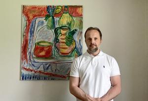 Carl Björkegren, 45, är egen företagare. Här med en av de tavlor som hans pappa målade när familjen bodde i Sandviken. Bild: Privat.