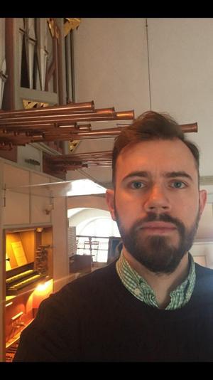 Henrik Berg framför orgeln i Boda kyrka. Foto: Privat