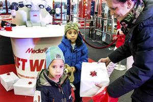 Albert och John Engström, tre och sex år, har handlat en julklapp till pappa tillsammans med mamma Cathrin Thelberg Engström. De såg på när roboten slog in paketet.