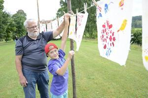 Med gemensamma krafter hänger morfar Curt Fernquist och barnbarnet Rasmus Karlsson upp tygstycket med schablontryck där det får torka.