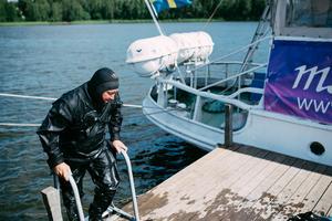 Dykare undersöker båtens botten efter skador.