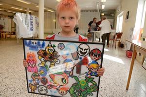 Pärltavla. Vidar Aronsson visar en tavla som brodern Oliver Voigt gjort av pärlor.