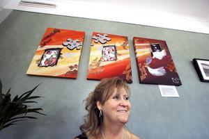 Maija Luuk. I bakgrunden några av hennes målningar som kan ses på diakonicentrums kafé i Örebro. BILD: LG MÅNZON
