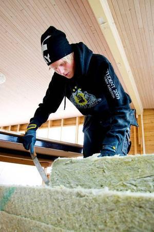 Robin Karlsson skär ut isolering till serveringens väggar.
