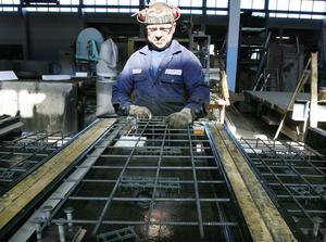 Joakim Hallgren, Görvik, är en av de fem anställda som från mitten av maj till oktober byter arbetsmiljö – från fabrik till fjäll, och jobbar ute på plats med de stora vindkraftsprojekten. Här lägger han ut armering inför gjutning av stödmurar till Ådalsbanan.