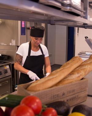 Tina Berg Dahlström  jobbar bland bröd och grönsaker.